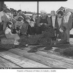 Children watching fisherman Hegerberg repair net at Fisherman's Terminal, Seattle, 1949